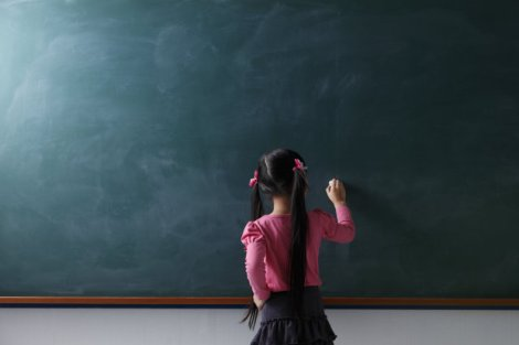 113886470 girl writes on chalkboard